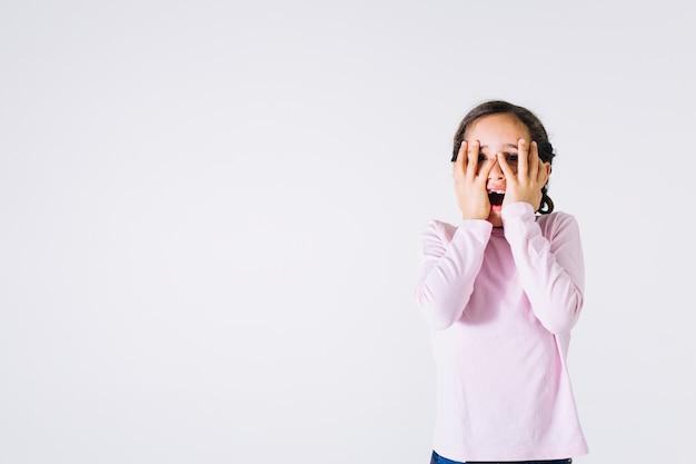Menina assustada, cobrindo o rosto