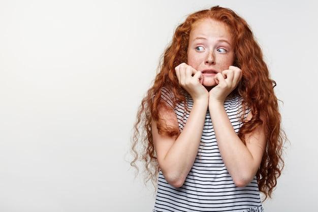 Menina assustada com cabelo ruivo e sardas, com medo e ansiosa roendo as unhas dos dedos, olhando para a câmera com os olhos bem abertos e desviando o olhar, isolada sobre um fundo branco com espaço de cópia.