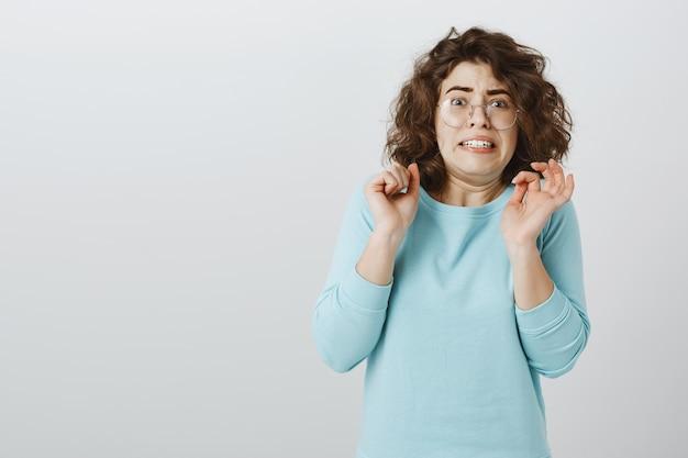 Menina assustada e tímida olhando com aversão, encolhendo-se ou fazendo careta de nojo