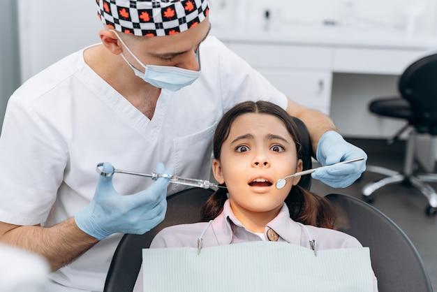 Menina assustada em uma cadeira odontológica, com medo da injeção. o dentista segura uma seringa com uma agulha na mão.