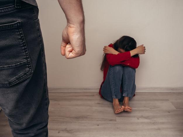 Menina assustada em uma camisa vermelha contra a parede e homem com os punhos apertados