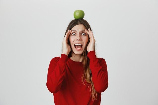 Menina assustada gritar em pânico como ver flecha voadora, segurando o alvo de maçã na cabeça