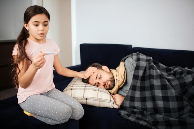 Menina assustada sentada além do pai doente. ela olha para o termômetro e se pergunta. jovem dorme. ele está doente e tem temperatura.