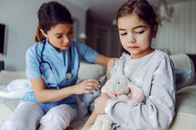 Menina assustada sentada no sofá tomando vacina