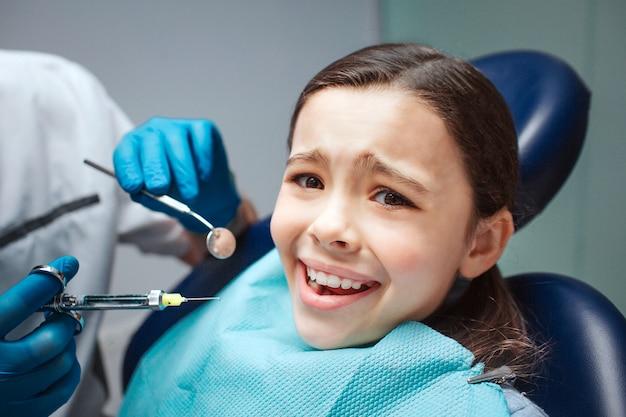 Menina assustada sentar na cadeira odontológica