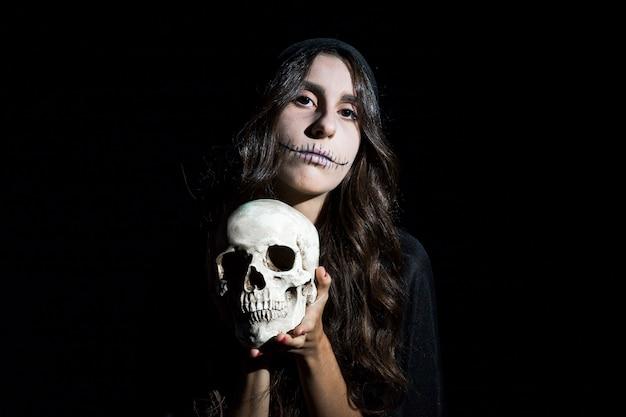 Menina assustadora com crânio humano