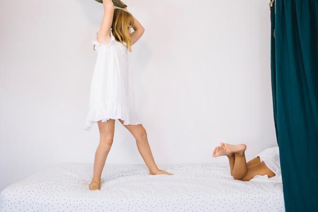Menina atingindo a irmã com travesseiro