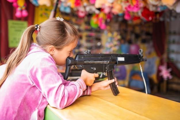 Menina atira de arma de brinquedo infantil no centro de entretenimento infantil