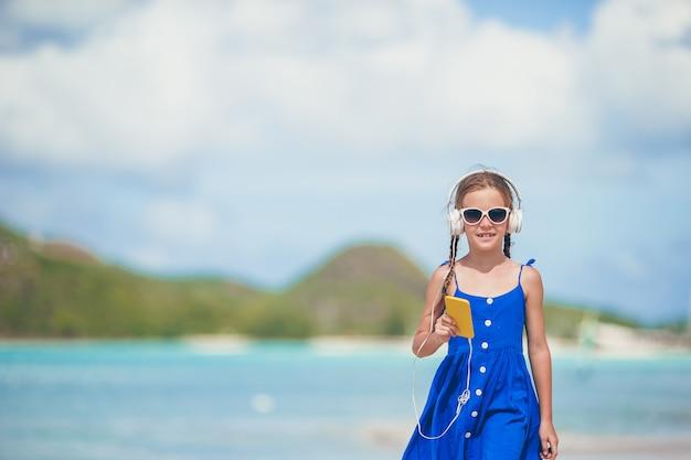 Menina ativa adorável na praia durante as férias de verão