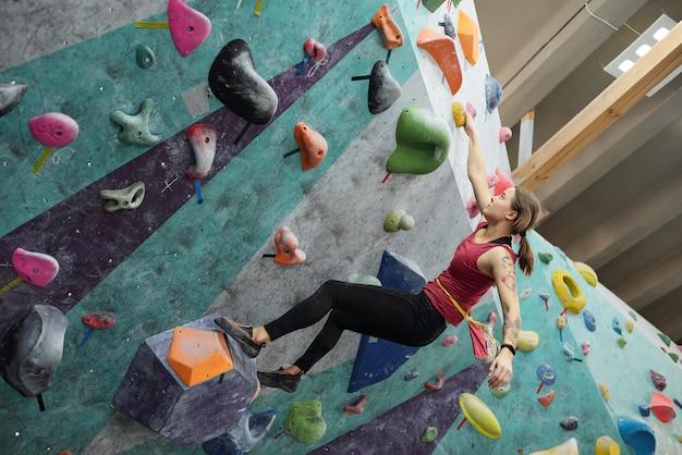 Menina ativa em roupas esportivas segurando-se por uma das pequenas pedras ao longo do equipamento de escalada enquanto pratica exercícios difíceis