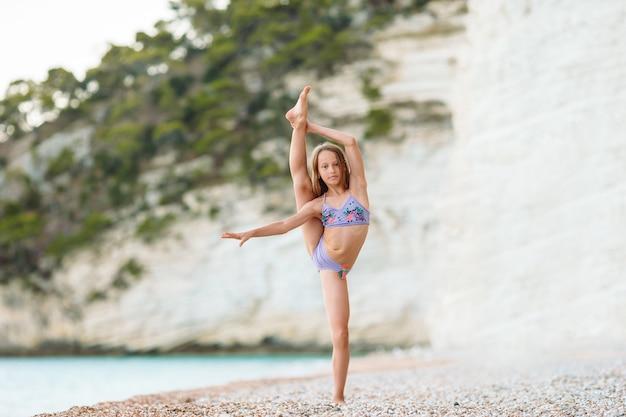Menina ativa na praia se divertindo muito. garoto bonito fazendo exercícios desportivos à beira-mar