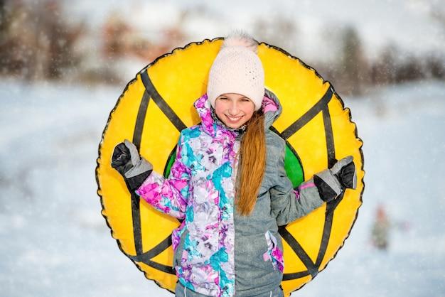 Menina ativa positiva que guarda a tubulação de neve atrás dela