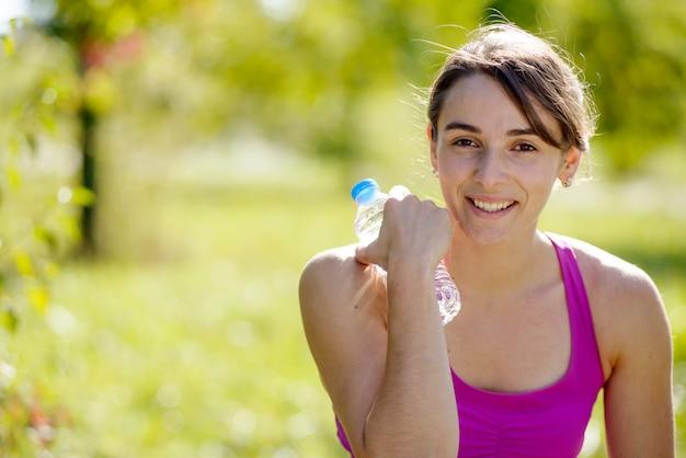 Menina atlética água potável após o exercício