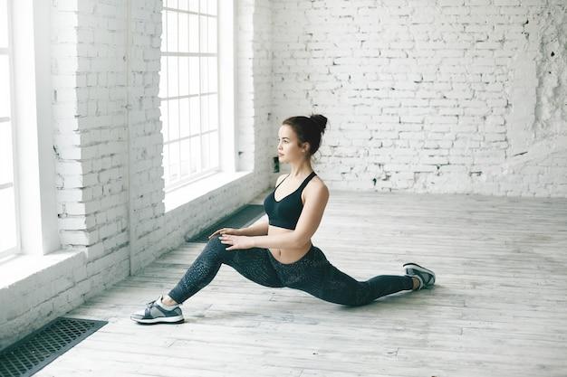 Menina atlética apta com coque de cabelo, esticando as pernas após o treinamento de força em luz espaçosa sala de ginástica. mulher jovem e bonita vestindo roupa esportiva da moda, praticando fendas no chão perto da janela