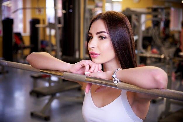 Menina atlética bonita nova perto da barra no gym.