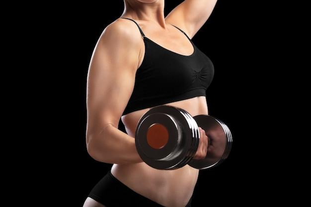 Menina atlética com halteres na mão, isolados no preto.