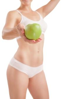 Menina atlética com maçã verde na mão.