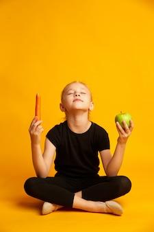 Menina atlética de sete anos segurando a maçã verde e cenoura nas mãos isoladas em amarelo