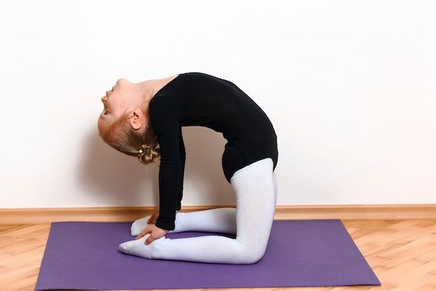 Menina atlética fazendo exercícios de alongamento em uma esteira roxa