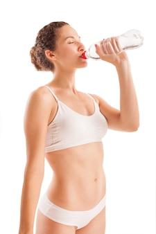 Menina atlética magra bebe água de uma garrafa isolada no branco.