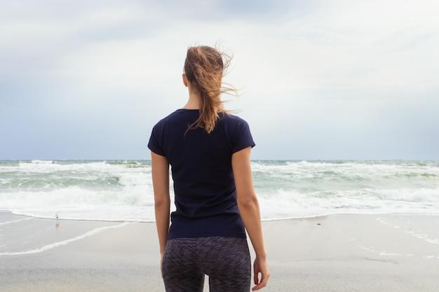 Menina atlética no sportswear em pé na praia e olhando para as ondas do mar