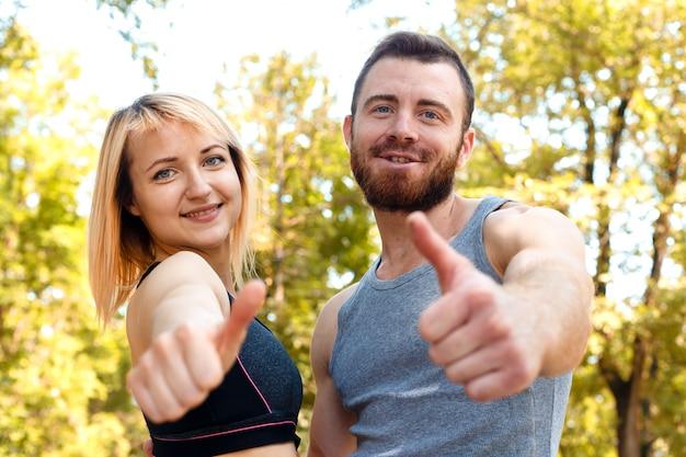 Menina atlética nova e homem de barba no treinamento olhando para a câmera, mostrando os polegares para cima, assinar ..