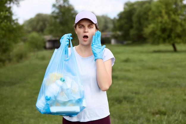 Menina atônita com a boca amplamente aberta fica com saco de lixo na mão, mantendo a palma da mão na bochecha