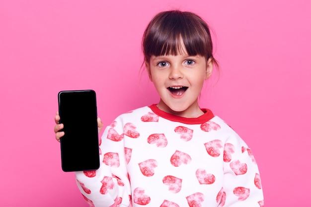 Menina atônita segurando um telefone inteligente com tela em branco, com expressão facial de surpresa e boca aberta, posando isolado sobre a parede rosa.