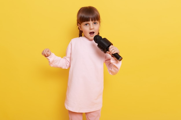 Menina atraente com microfone cantando sua música favorita, olha para a câmera com a boca aberta, vestindo uma camisa rosa pálida, encostada na parede amarela, pequena vocalista canta.