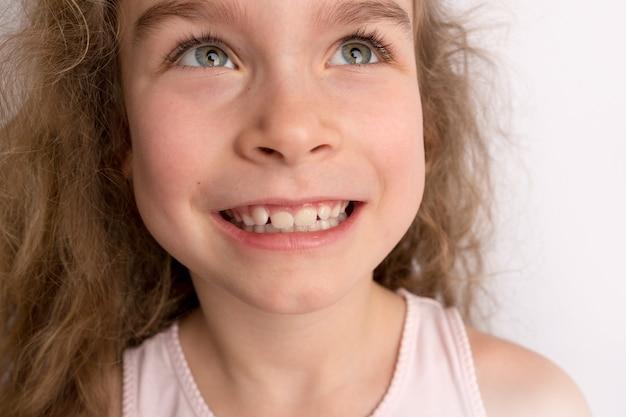 Menina atraente fica em um fundo branco, expressão feliz no rosto com um lindo sorriso, dentes tortos de crianças, odontopediatria. foto de alta qualidade