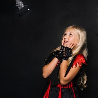 Menina atraente incompreensível pelo brinquedo de morcego