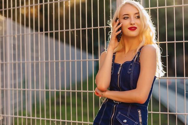 Menina atrativa loura emotiva nos óculos de sol com o telefone no sol do verão urbano