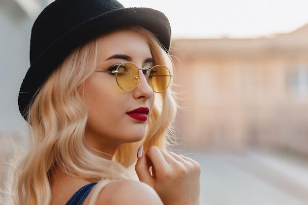 Menina atrativa loura nos óculos de sol e no chapéu à moda no sol do verão urbano