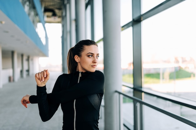 Menina atrativa no sportwear preto que estica os braços. fechar-se.