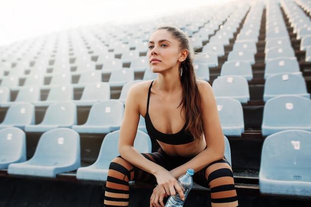 Menina atrativa nova desportiva no sportswear que relaxa após o exercício duro