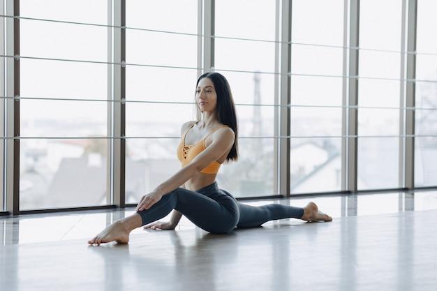 Menina atrativa nova que faz exercícios da aptidão com ioga no assoalho contra o fundo de janelas panorâmicos