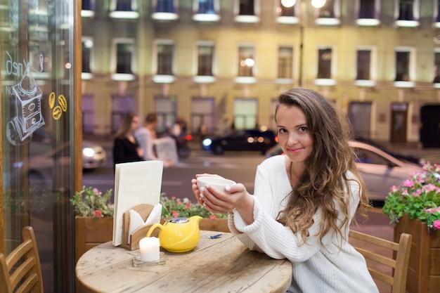 Menina atrativa nova que senta-se na noite em um café.