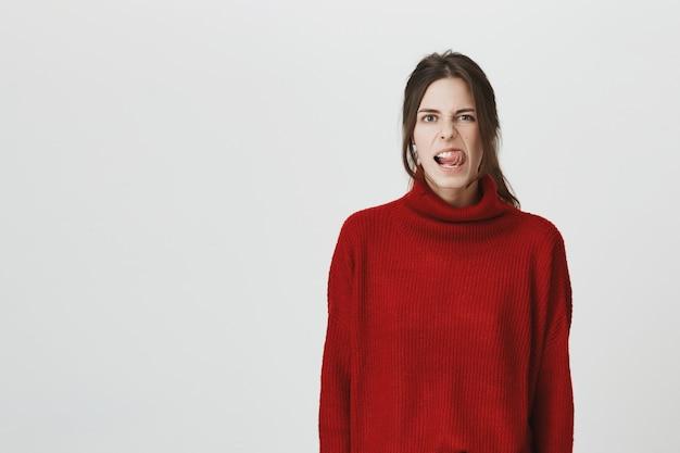 Menina atrevida atrativa que mostra a língua