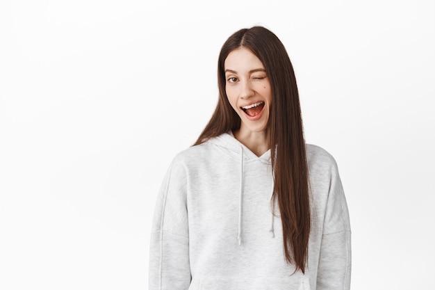 Menina atrevida positiva piscando e sorrindo, insinuando algo, encorajando você, elogiando excelente escolha, fazendo insinuações maliciosas, encostada em uma parede branca