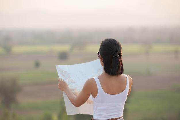 Menina aventureira navegando com um mapa topográfico nas belas montanhas.
