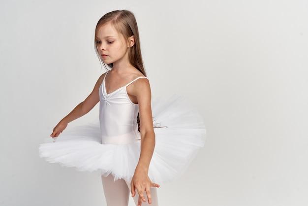 Menina bailarina com um tutu branco e sapatilhas de ponta