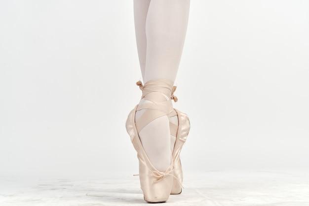 Menina bailarina em um terno branco e sapatilhas de ponta