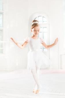 Menina bailarina em um tutu. criança adorável que dança o balé clássico em um estúdio branco.