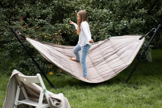 Menina balançando em pé em uma rede