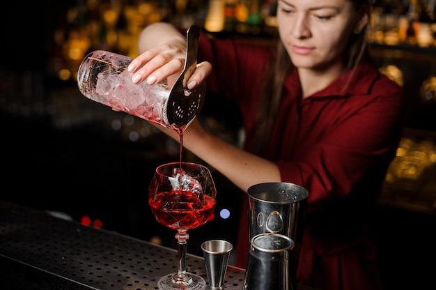 Menina barman, derramando um cocktail vermelho claro
