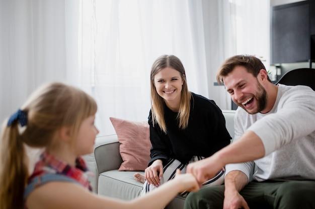 Menina batendo os punhos com os pais