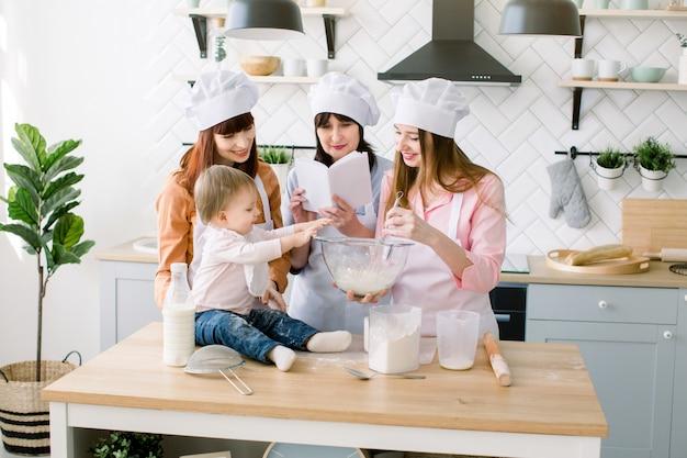 Menina bebê bonitinho ajuda a mãe, tia e avó a fazer uma massa juntos. avó lê receita de biscoitos do livro. família feliz assando na cozinha
