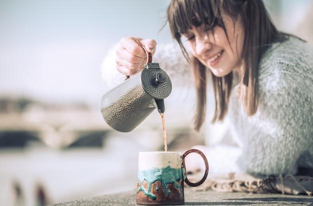 Menina bebe café e lê livro ao ar livre