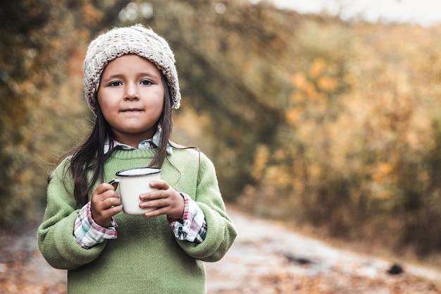 Menina bebe chá no parque de outono
