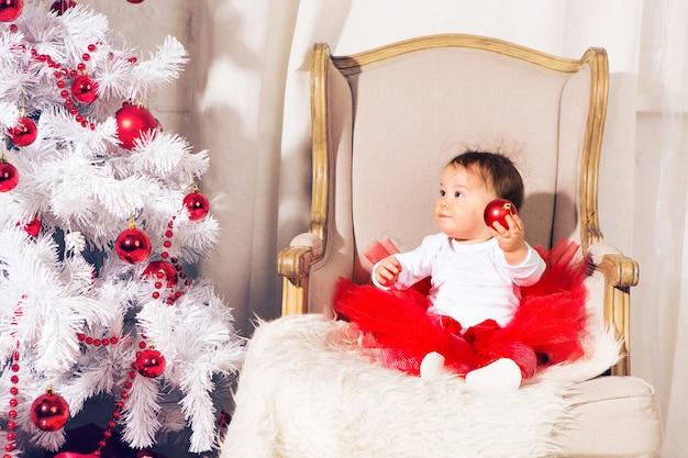 Menina bebê criança feliz perto de uma árvore de natal